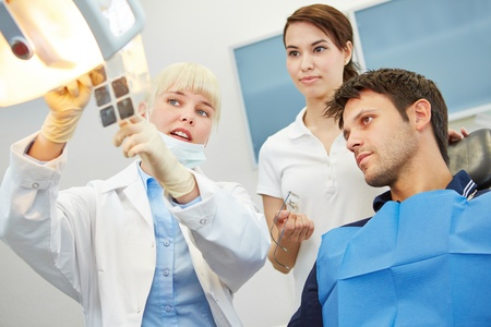 prosthetics: Female dentist showing caries on x-ray image to a patient before treatment Stock Photo