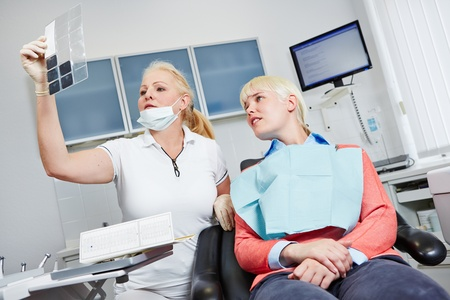 dental clinic: Dentist looking at x-ray image of teeth of a female patient