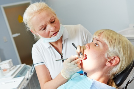 Patient sitting on chair at dentist for a dental treatment photo