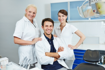 Happy group of employees at dentist with two dental assistants photo