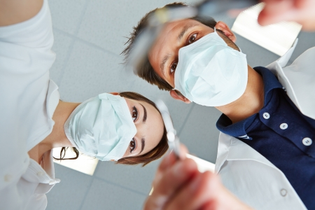 denture: Patient POV of dentist and dental assistant during dental treatment