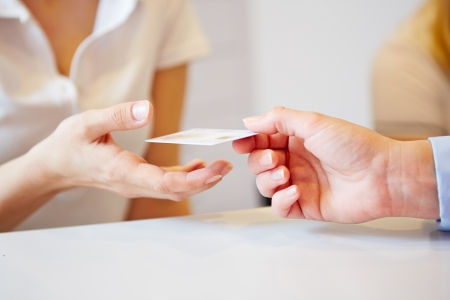 Hand of a patient giving smart card to doctors assistant Imagens