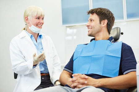 Female dentist talking with a patient on dental chair Stock Photo
