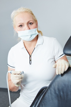 Dentist working with dental turbine and drill and mouthguard photo