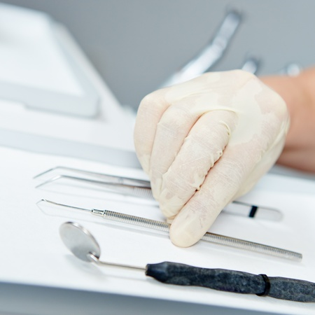 Hand of dentist reaching for probe for dental examination Stock Photo