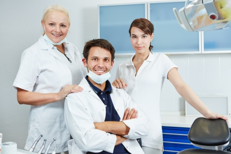 Happy dentist with his dental team in his dental practice photo