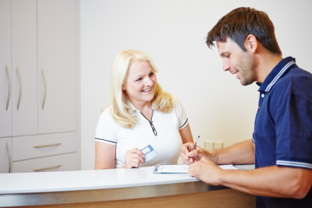 Patient talking with doctors assistant at the reception while filling out a form