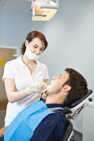 Male patient at dental examination with female dentist photo