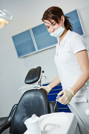 Dental assistant cleaning basin after dental treatment in dentistry photo