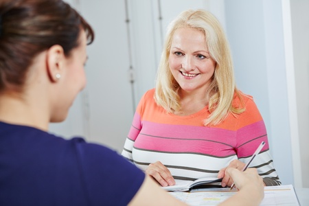 scheduling: Senior woman scheduling appointment for a doctor at reception