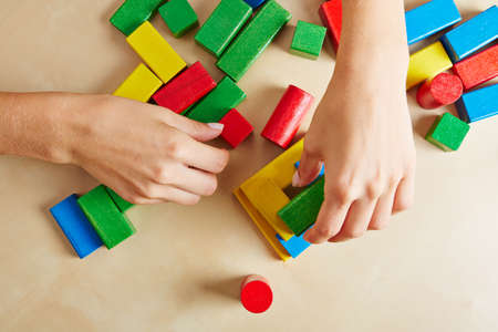 demented: Two female hands playing with colorful wooden building blocks Stock Photo