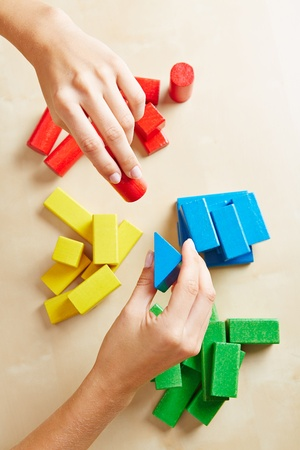 demented: Two female hands sorting building blocks by color Stock Photo
