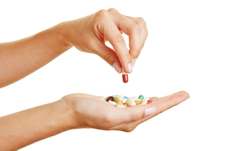 take medicine: Female hand holding a red pill over different medicine in palm of hand