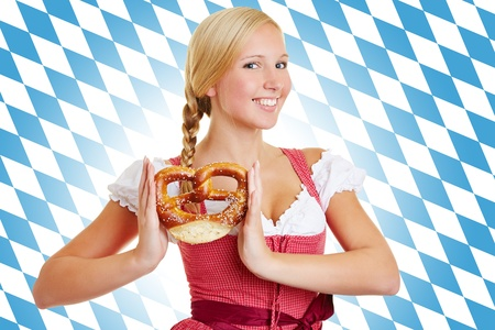 Smiling attractive woman with pretzel in a dirndl in front of Bavarian flag photo