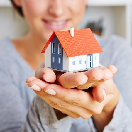 household insurance: Two hands of a woman holding a little house