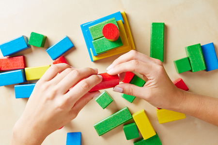 Two hands building a tower with colorful wooden building blocks photo