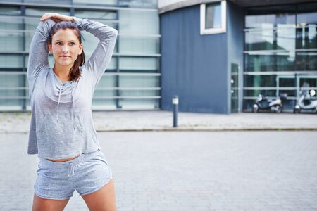 warm up: Sporty young woman warming up before running in the city Stock Photo