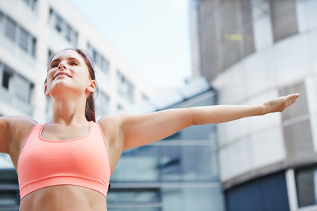 vital: Sporty woman doing breathing exercise for relaxation in the city Stock Photo
