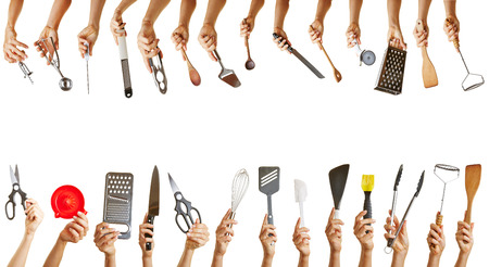 Frame with hands holding many different kitchen tools