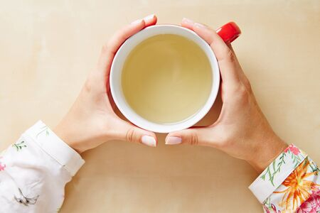 chamomile tea: Two hands holding chamomile tea in a cup from above
