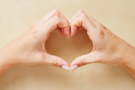 Female hands forming a heart shape with the fingers photo