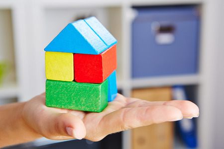 building blocks: Female hand holding colorful house made of building blocks Stock Photo