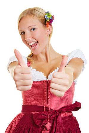 ambos: Mujer joven feliz en un dirndl sosteniendo ambos pulgares Foto de archivo