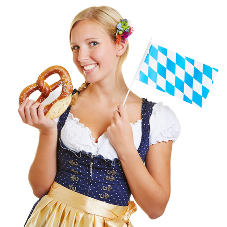 Happy young woman in a dirndl smiling with pretzel and a bavarian flag photo