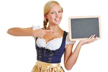 dirndl: Happy young woman in a dirndl pointing with her index finger to empty blackboard Stock Photo