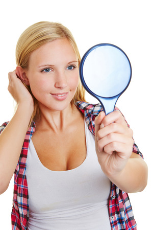 prettify: Young blond happy woman looking into a hand mirror Stock Photo