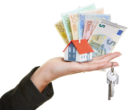 renter: Female hand holding little house, keys and Euro money bills Stock Photo