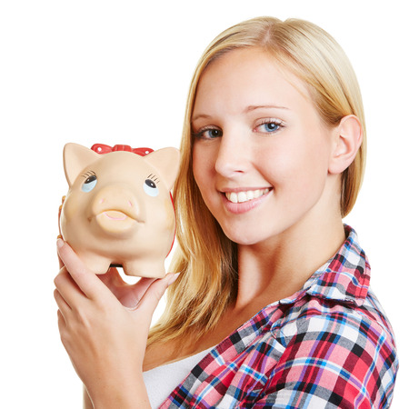 Happy young blond woman holding a piggy bank photo