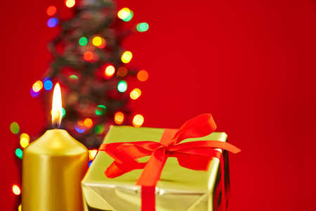 Christmas with candle, gift and christmas tree on a red background photo