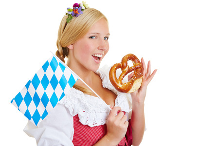 Happy young woman with a bavarian flag eating a fresh pretzel photo