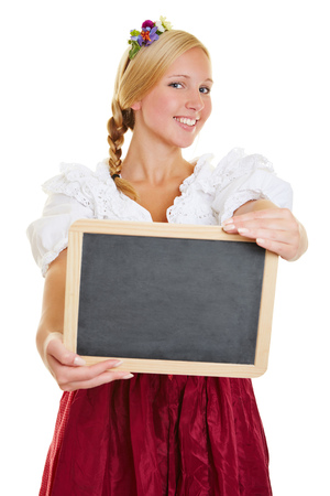 dirndl dress: Happy young woman with a dirndl holding an empty blackboard