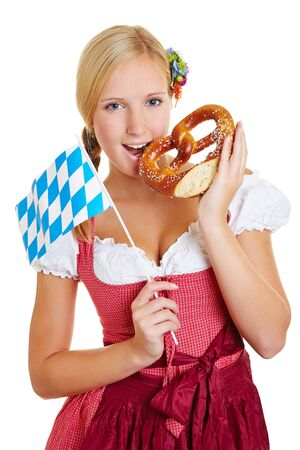 dirndl dress: Young happy woman in a dirndl with bavarian flag and pretzel