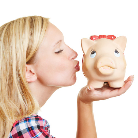 kissing lips: Blond young woman kissing a piggy bank with her lips Stock Photo