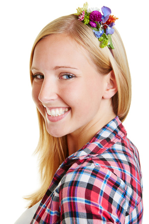 Face of a happy smiling young blond woman with flowers in her hair