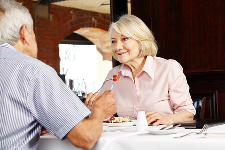 Elderly couple in restaurant talking to each other while eating Stock Photo - 22649013
