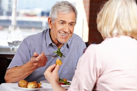 Happy senior couple eating in restaurant for lunch