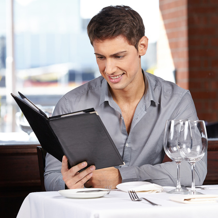 Smiling man looking at the drinks menu in a restaurant Stock Photo - 22649016