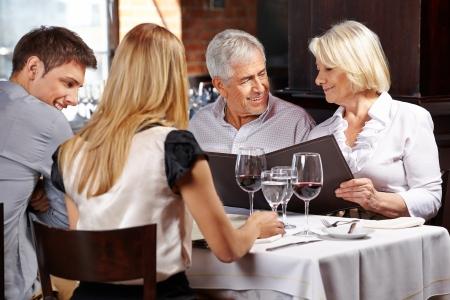 메뉴를 들고 레스토랑에서 두 고위 사람들과 가족