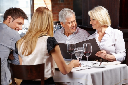 Family with two senior people in restaurant holding the menu photo