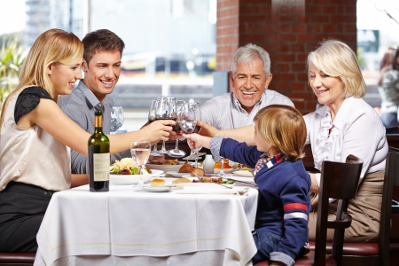 Happy family in a restaurant clinking their glasses of wine and water