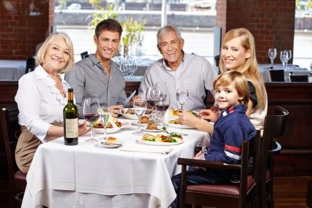 Retrato de una familia feliz y sonriente en un restaurante