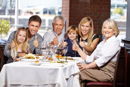thumb up: Happy family congratulate in restaurant holding their thumbs up
