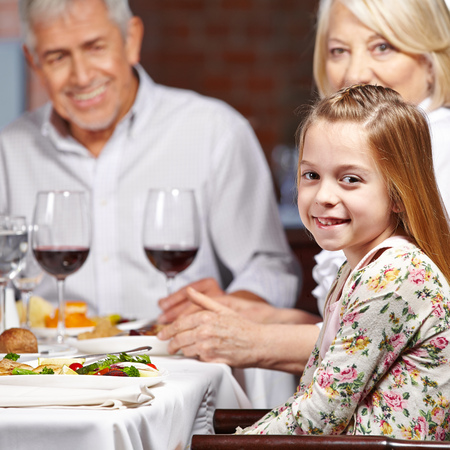 Two happy grandparents with their grandchild eating in a restaurant