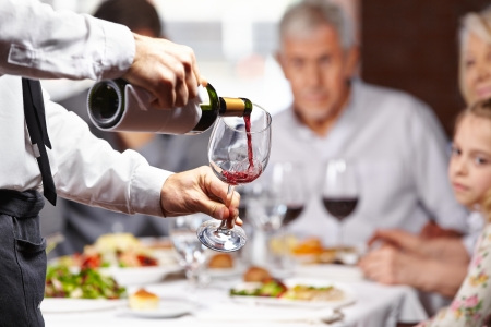 meseros: Camarero verter el vino tinto en una copa en una mesa de restaurante