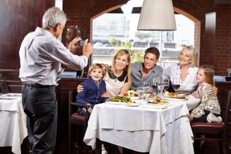macht: Opa macht ein Familienfoto beim Restaurantbesuch mit dem Smartphone Stock Photo