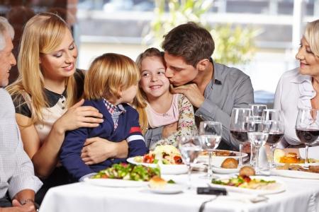 familia comiendo: Padre que besa a su hija en el restaurante, mientras que comer fuera con la familia